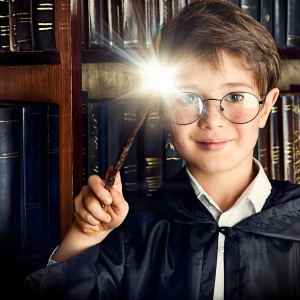 A boy stands with magic wand in the library by the bookshelves w